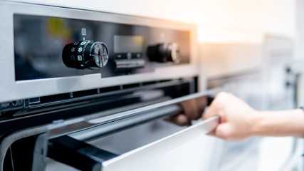 Obraz Male hand opening oven door in the kitchen showroom. Buying cooking appliance for domestic kitchen. Home improvement concept - fototapety do salonu