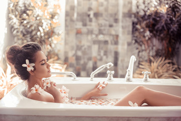 Pretty girl enjoying bath with plumeria tropical flowers. Health And Beauty. Spa Relax. Closeup Beautiful woman Bathing With Petals. Treatment, Aromatherapy Skin Body Care Therapy.