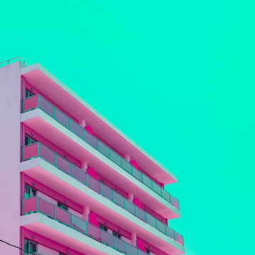 Pink hotel and green sky in infrared style. Tropical travel concept. Minimalism