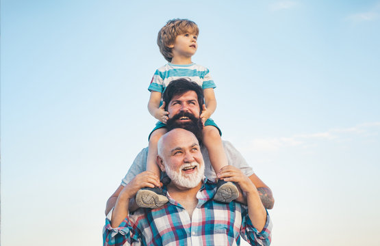 Men generation: grandfather father and grandson are hugging looking at camera and smiling. Fathers day concept. Generation concept. Weekend family play. Men in different ages.