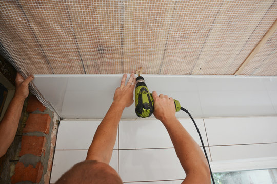 Contractors installing white PVC Ceiling Boards with screw gun in the bathroom