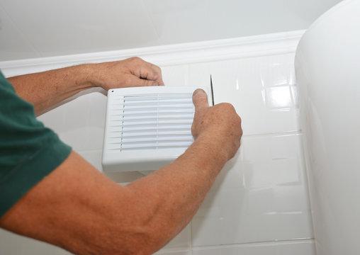 Bath fan repair, installation. Handyman installing new bath vent fan, ventilation system in the house bathroom