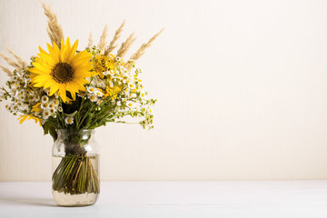 Field flowers in a glass vase. Summer bouquet of flowers on the white background