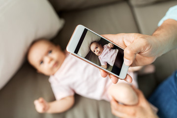 family, technology and fatherhood concept - close up of middle aged father with smartphone taking picture of his little baby daughter lying on sofa at home