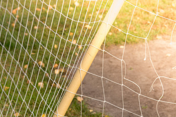 Iron gate with white net on grass for playing football.