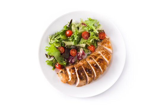 Grilled chicken breast with vegetables on a plate isolated on white background. Top view