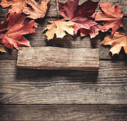 autumn background with signboard, orange leaf on old grunge wood deck, copy place for inscription, Top view, tablet for text.