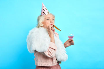 Elderly beautiful woman blowing a party horn, holding a glass of juice, against blue background,celebration, happiness concept