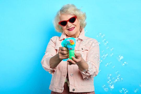 funny positive granny in sunglasses wearing stylish clothes enjoying making bubbles. close up portrait. isolated blue background. studio shot.