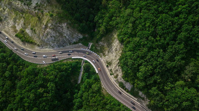 Drones Eye View - winding road from the high mountain pass in Sochi, Russia. Great road trip trough the dense woods.