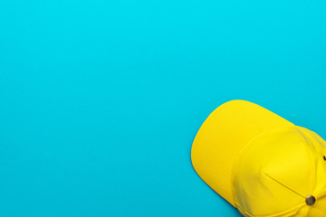 Minimalist flat lay photo of the bright yellow cap with copy space. Top view of the yellow baseball cap over the blue turquoise background.