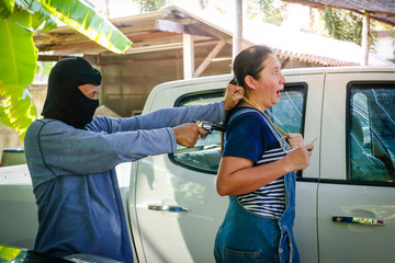 The robbers wore a black mask, carrying a gun, robbing a gold necklace from a woman who was about to open the car door.