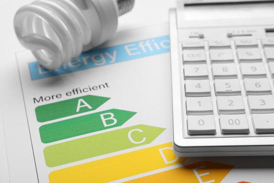 Energy efficiency rating chart, fluorescent light bulb and calculator, closeup