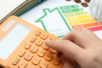 Woman with calculator and energy efficiency rating chart at table, closeup