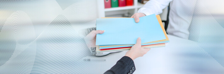 Secretary putting files in the hand of a businessman; panoramic banner