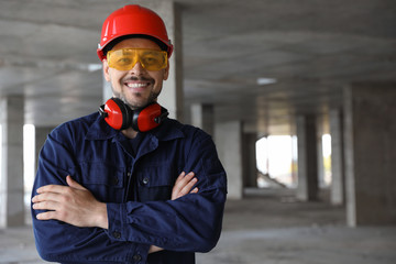 Professional engineer in safety equipment at construction site, space for text Fototapete
