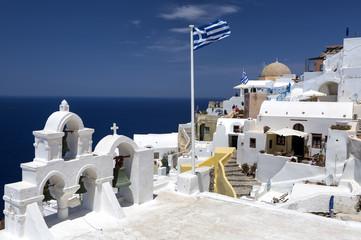 Greek flag and four bells in Oia, Santorini, Greece.