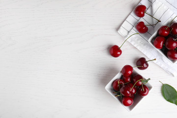 Fototapete - Flat lay composition with sweet cherries on white wooden table. Space for text