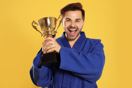 Portrait of happy young man in blue kimono with gold trophy cup on yellow background