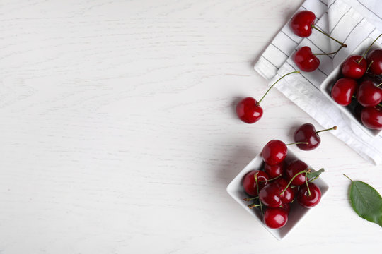Flat lay composition with sweet cherries on white wooden table. Space for text