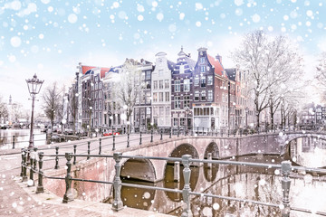 Traditional Dutch old houses and bridges on the canals in Amsterdam on a snowy winter night, The Netherlands Wall mural