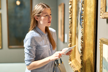 Portrait of young woman with a guide looking at pictures at museum of arts