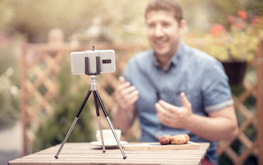 Blogger speaking and gesturing in front of camera. Selective focus on smart phone mounted on a tripod. Man making the next youtube episode on a restaurant terrace
