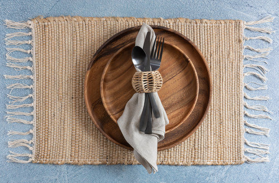place setting on woven fiber placemat on blue background with two stacked wooden plates and linen napkin with black metal flatware and wicker napkin ring