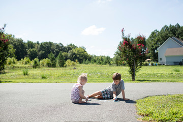 Cute Blonde Siblings Color with Chalk on Driveway in Summertime