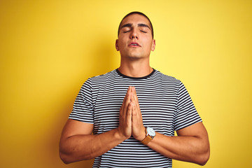 Young handsome man wearing striped t-shirt over yellow isolated background begging and praying with hands together with hope expression on face very emotional and worried. Asking for forgiveness.