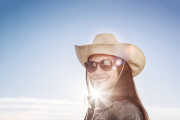 Bright sunbeam shines on face of beautiful young girl in cowboy style wide brimmed hat, blue sky background