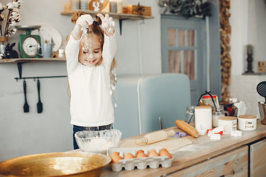 Child in a kitchen. Little girl with a dough.