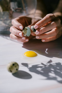 breaking egg yolk on marble. quail egg shell in hand.