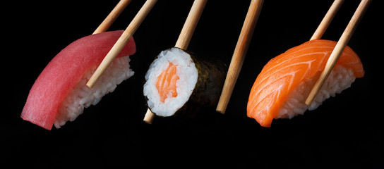 Fotobehang Sushi bar Traditional japanese sushi pieces placed between chopsticks, separated on black background