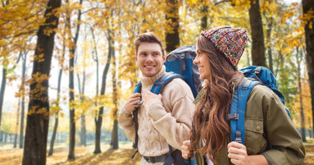 adventure, travel, tourism, hike and people concept - couple of travelers with backpacks over autumn park background