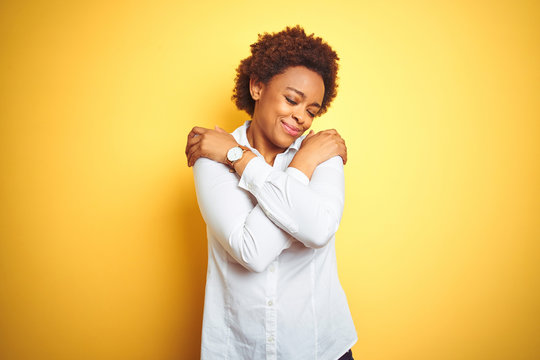 African american business woman over isolated yellow background Hugging oneself happy and positive, smiling confident. Self love and self care