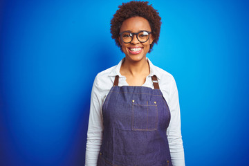 Young african american woman shop owner wearing business apron over blue background with a happy and cool smile on face. Lucky person.