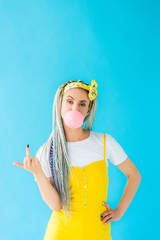 girl with dreadlocks blowing bubblegum and showing middle finger on turquoise