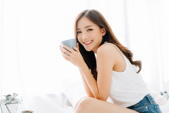 Happy smiling beautiful Asian woman awaking with cup of coffee and looking at camera in the bedroom. Lazy day off concept