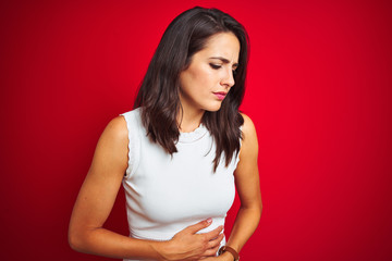 Young beautiful woman wearing white dress standing over red isolated background with hand on stomach because nausea, painful disease feeling unwell. Ache concept.