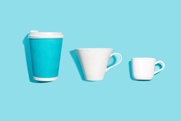 Coffee pattern of white ceramic and blue paper cup for coffee on bright blue background. Pop art minimal flat lay style design, creative concept of diversity. Top view. Copy space. Banner.