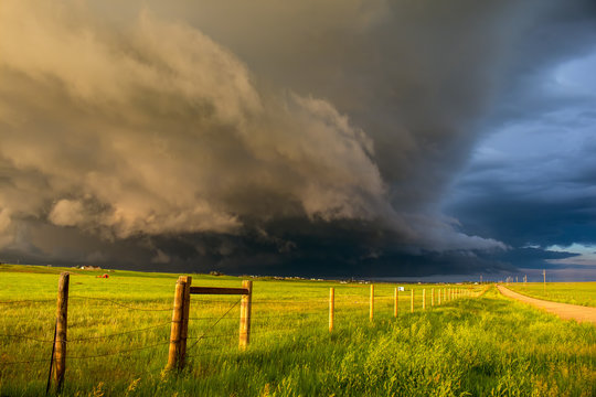 A dark shelf cloud and storm approach as the sun shines brightly looking down a fence in the rural countryside.