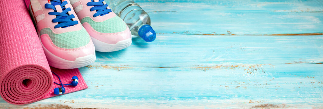Pink yoga mat, sport shoes, bottle of water and earphones on wooden background. Healthy lifestyle, yoga, sport, dieting concept. Trendy female sport equipment. Copy space, long format
