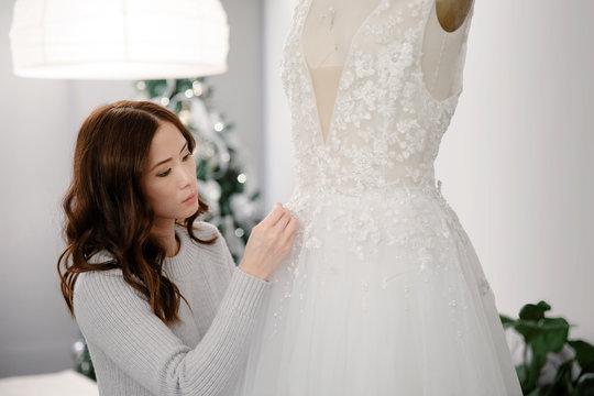 Designer tailoring wedding dress on dress form
