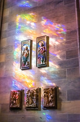 Colorful light of stained-glass window over saints illustrations on the wall of old church