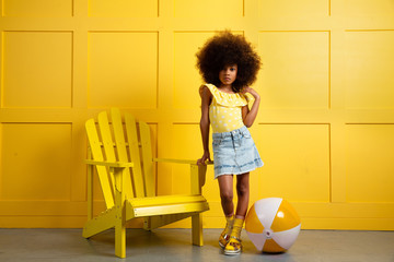Young girl poses in yellow themed setting