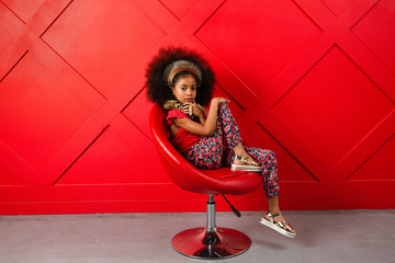 Young girl poses in red themed setting Wall mural