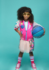 Girl in tutu and sunglasses poses with basketball