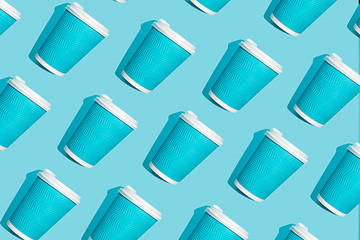Coffee pattern of blue paper cup for coffee on bright blue background. Pop art minimal flat lay...