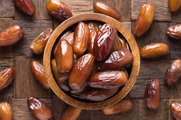 dried date fruit in wooden bowl, top view.